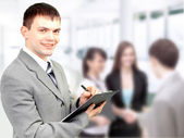 Portrait of confident business man holding document with team in — Stock Photo