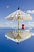 White umbrella and apple on mirror — Stock Photo