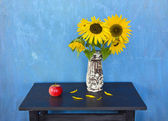 Still life with apple and sunflowers — Stock Photo