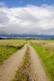 Countryside road and autumn rain clouds — Stock Photo