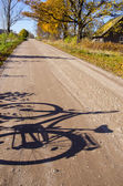 Countryside road with bicycle shadow — Stock Photo