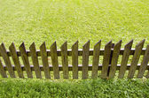 Wooden fence and green grass — Стоковое фото
