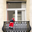 Snowman climbing on the house balcony — Stock Photo