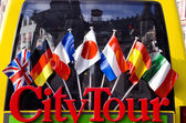 City tour bus for tourists detail with flags — Stock Photo