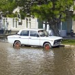 Stock Photo: Abandoned car in deep pool near building