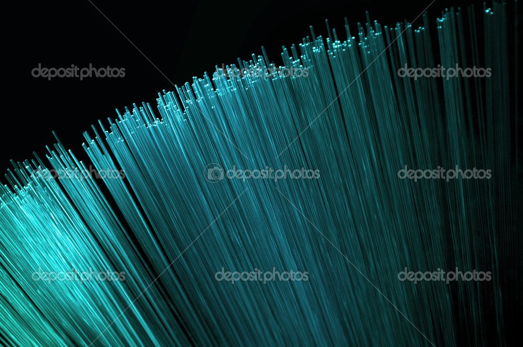 Abstract style close up on the ends of many bright cyan illuminated fiber optic light strands arranged over black.    #6832583