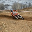 Motorbike racer turns sharply to the on a sandy track — Stock Photo