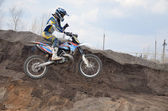 Motocross rider jumps over an earthen pit with one hand — Stock Photo
