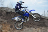 Motocross rider on the motorbike takes off on a high mound of ea — Stock Photo