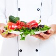 Chef holding plate with vegetables — Stock Photo #6957979