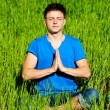 Young man meditation on green grass — Stok fotoğraf