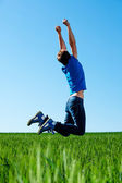 Man jumping on the green field — Stock Photo