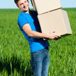 Man in blue t-shirt carrying boxes -  