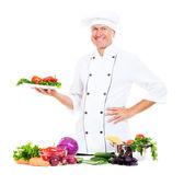 šéfkuchař drží desku s čerstvou zeleninou — Stock fotografie
