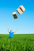 Man catching boxes on green field — Stock Photo