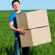 Foto de Stock  : Min blue t-shirt carrying boxes