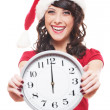 Laughing girl with santa hat holding clock — Stockfoto