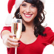 Woman in santa hat holding glass of champagne — ストック写真
