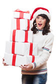 Amazed woman in santa hat holding gift boxes — Stock Photo