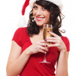 Woman in santa hat holding glass of champagne - Stok fotoğraf