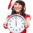 Excited girl with santa hat holding clock - Stok fotoğraf