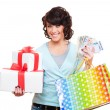 Cheerful young woman holding paper money and gifts - Stockfoto
