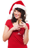Woman in santa hat holding glass of champagne — Stock Photo