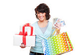 Cheerful young woman holding paper money and gifts — Stock Photo