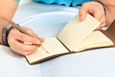 Hand and notebook. Close up — Stock Photo