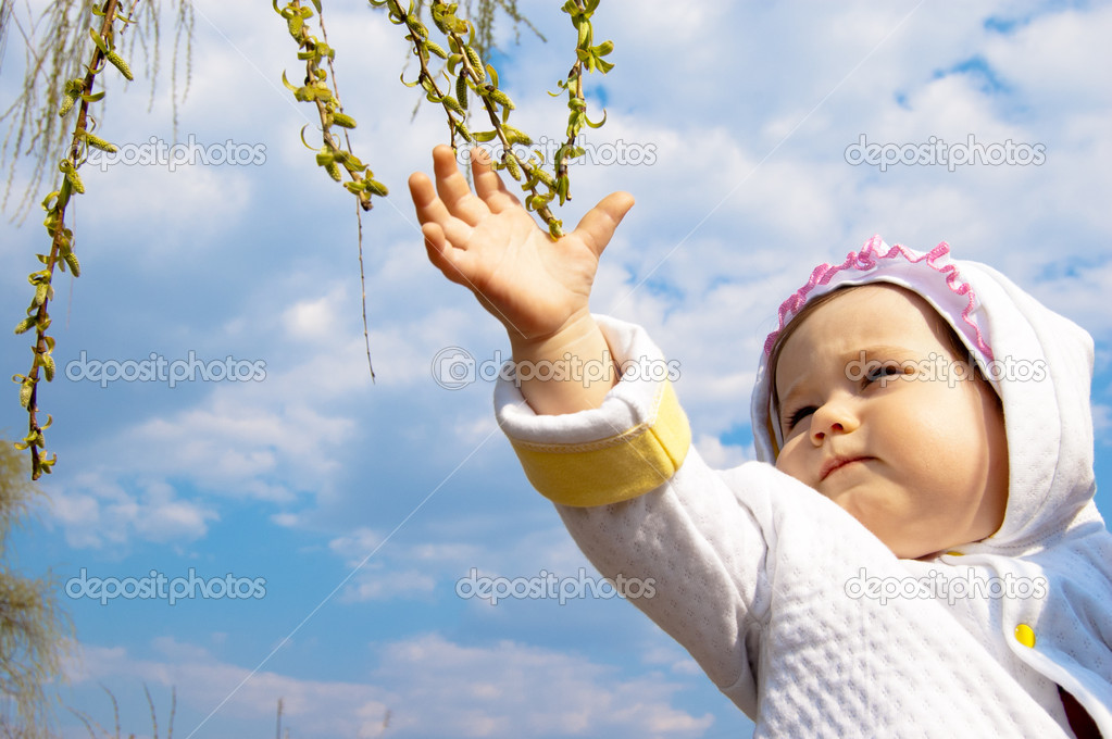 Little girl touching green buds on blue sky background — Stock Photo #6863287