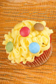 Fancy yellow cupcake with confectionery — Stock Photo