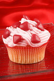 Cupcake with red sugar-coated hearts — Stock Photo