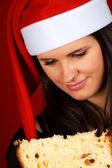Santa Claus girl eating panettone — Stock Photo