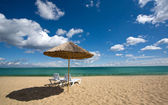Two chairs and umbrella on the beach — Stock Photo