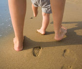 Mother and child walking on a sandy beach — Stock Photo