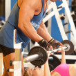 Trainer assisting woman at gym - Stock Photo