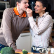 Young couple making and tasting salad — Stock Photo