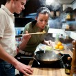 Young couple preparing lunch in kitchen — Stock Photo