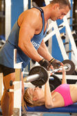 Trainer assisting woman at gym — Stock Photo