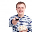 Young man with popcorn and remote control sitting on the floor isolated on white — Stock Photo #7939957