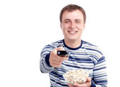 Young man with popcorn and remote control sitting on the floor isolated on white — Stock Photo