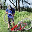 Bike repair. Young man repairing mountain bike in the forest — Stock Photo #7940076