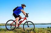 Active bicyclist at the riverside — Stock Photo
