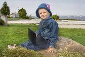 La chica en el parque con un reproductor de vídeo portátil — Foto de Stock