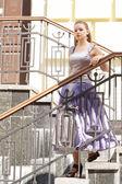 Hermosa chica en hermosos vestidos en las escaleras — Foto de Stock