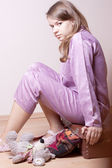 The girl in purple pajamas sitting on a suitcase — Stock Photo