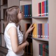 Beautiful girl in the library — Stockfoto