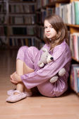 The girl in pink pajamas in the library — Stock Photo