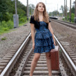 Girl with a suitcase standing on the rails — Stock Photo
