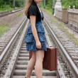 Girl with a suitcase standing on the rails — Stock Photo #7579727